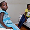 Sarah Nyiramana Bayavuge, 6,  and her sister Lea Nyiramahoro, 11, sit in their new bedroom. They are refugee from the Democratic Republic of Congo who recently settled in Lowell after living in a refugee camp for decades in Uganda with their family. SUN/JOHN LOVE