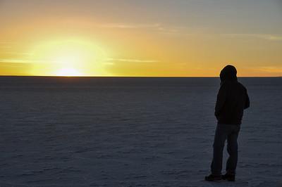 Man starring at the sunset in Salar de Uyuni, Bolivia