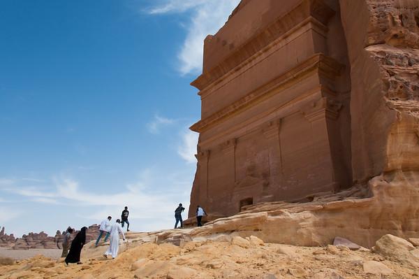 People entering a Nabatean tomb in Madain Saleh archeological site, Saudi Arabia