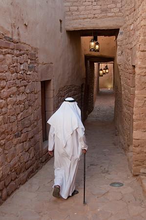 Saudian walking inside the walls of Al-Ula Old City, Saudi Arabia