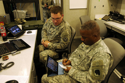 In this image released by the Texas Military Forces, Sgt Jahsen Dilger provides instruction to Lt Col Dedrick Hoskins, the deputy J6 for Oklahoma's Joint Task Force, on how to remotely access Defense Connect Online to improve mission communications and information distribution during Operation Sooner Response November 15, 2011. The event featured six states engaging simulated disaster incidents throughout five sites in Oklahoma. Texas Soldiers supported the mission by contributing the 6th Civil Support Team and personnel assets from the FEMA Region VI Homeland Response Force.