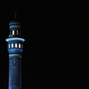 A minaret of the Al Saddiyah mosqe against the night sky in Mutrah, Oman