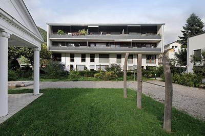 01 Baugemeinschaft Wohnhof Golfstraße, Gutach im Breisgau. Blick vom Gemeinschaftsgarten auf die Süd-West Fassade des Mehrfamilienhauses