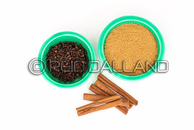 Organic Brown Sugar and Cloves in Green Fiesta Ware Bowls with Cinnamon on White.