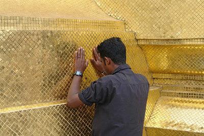 Dieser Mann betet an einer wand des Palastes.