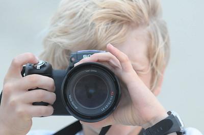 Oskar hat viel Spaß beim Photographieren. Er hat zur Kommunion eine neue Kamera bekommen, aber die hat Papa kaputt gemacht. Dann darf er natürlich Papas alte Kamera mal benutzen.