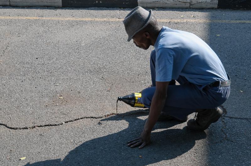 """Dieser Mann repariert die Strasse mit """"Kleber"""" aus der Flasche."""