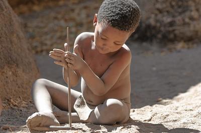 Dieser Junge spielt mit Stöcken. Er übt, wie man damit Feuer macht.