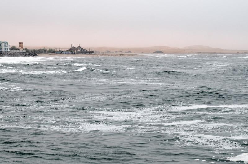 Vorne das Meer. Im Hintergrund sieht man die Dünen der Wüste.