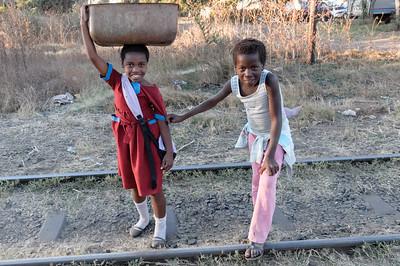 Schon die kleinen Kinder lernen, Lasten auf dem Kopf zu transportieren.
