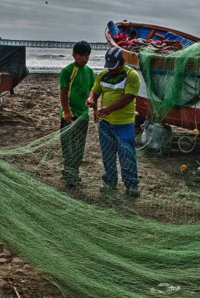Nadat deze vissers uren doorgebracht hebben op de koude zee volgt de taak van het herstellen van de visnetten en het nodige onderhoud van de boot.<br /> Opgejaagd door steeds meer eisende managers zullen die vissers wel niet zijn. <br /> <br /> Strand - Pimentel - Chiclayo - Lambayeque - Peru