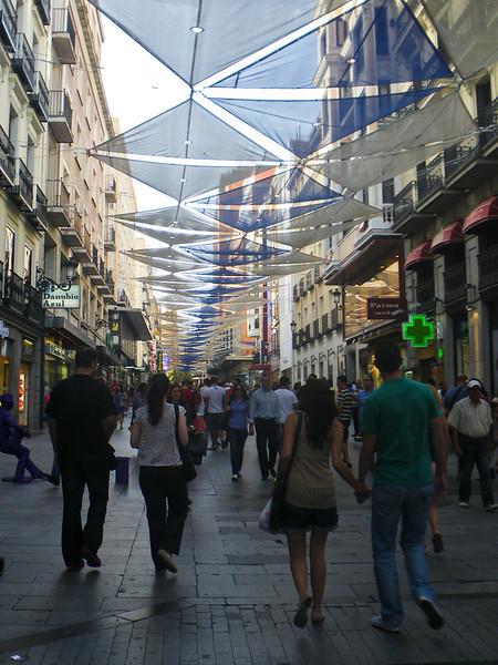 Zonnewering is welkom in één van de drukste winkelstraten van de Spaanse hoofdstad die er vandaag half verlaten bijligt. De Madrilenen nemen meestal in augustus vakantie en ontvluchten hun stad vaak naar de Spaanse costas. <br /> <br /> C/. Preciados - Puerta del Sol - Madrid - Spanje