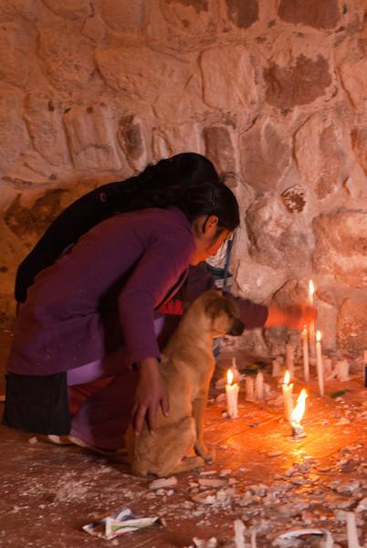 Devote moeder en dochter met de hond die een schietgebedje doen en een kaars aansteken.