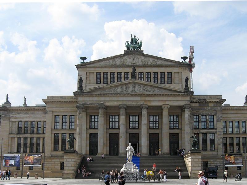 Konzerthaus op de Gendarmanmarkt,<br /> gelegen tussen links de Deutscher Dom en rechts de Französischer Dom. Deze twee kerken <br /> aan weerszijden van het plein lijken redelijk op elkaar, maar zijn op details na en wat betreft <br /> kerkgemeenschap verschillend. Dit gebouw stamt uit het begin van de negentiende eeuw en<br /> doet nog steeds dienst als concertgebouw. Liefhebbers kunnen hier genieten van het vaste <br /> symfonieorkest, het Konzerthausorchester Berlin.<br /> Bovenop de facade staat een beeld van Apollo in een strijdwagen voortgetrokken door griffioenen.<br /> De andere beelden op het gebouw verwijzen naar toneel en muziek.