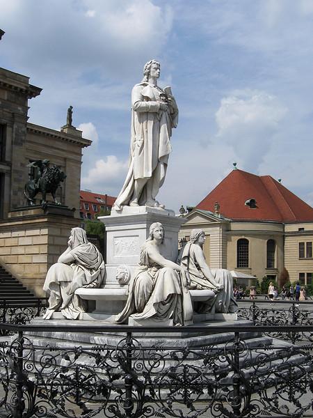 Voor het Concertgebouw staat sinds 1869<br /> een glimmend witmarmeren standbeeld van Friedrich Schiller,<br /> vervaardigd door Reinhold Begas.<br /> In de jaren dertig van de vorige eeuw werd het door de nazi's verwijderd,<br /> maar in 1988 is het teruggeplaatst.<br /> Het beeld staat op een hoog voetstuk en is omgeven door figuren die de<br /> Lyrische Poëzie, de Toneelkunst, de Filosofie en de Geschiedenis verbeelden.