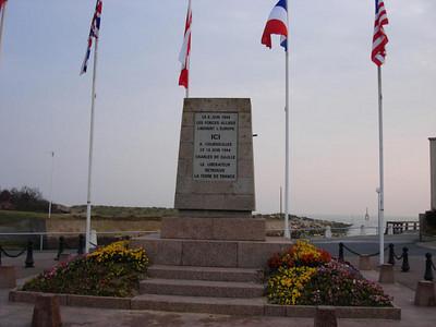 Courseulles-sur-Mer  Op 6 juni 1944 om 07.45 uur werden amfibietanks van de 1e Hussars gelanceerd in de oceaan op 3 km van de kust. Diegenen die erin slaagden het strand te bereiken, openden onmiddellijk het vuur op de Duitse posities. Zij gaven de 7e Brigade de gelegenheid om vlug in het binnenland vooruit te gaan en om Courseulles-sur-Mer in enkele uren te bevrijden. Tegen de avond waren 21.500 mannen en 3.200 voertuigen geland op Juno Beach. Hier is het bevrijdingsmonument ter herinnering aan de landing van de geallieerden op 6 juni 1944 te zien