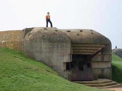 Batterij Longues sur Mer :  Deze batterij is een mooi bewaard gebleven onderdeel van de Duitse Atlantic-wall.  Met de bouw van deze vier M272 geschutsopstellingen werd gestart in september 1943.  In mei 1944 was de stelling gereed voor actie. Voor iedere kazemat was 600 m3 beton nodig en vier ton stalen bewapening. De twee meter dikke wanden en plafond waren bestand tegen geallieerde bombardementen. Om verzakking door een nabij-treffer tegen te gaan was er een zware basisfundering gemaakt.  De haken aan de bovenzijde dienden om de camouflagenetten aan te bevestigen.  Elke kazemat bevatte een snel vurend scheepskanon (150 mm) dat een bereik van 20 km had.