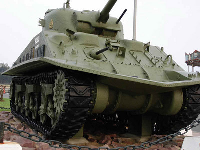 Sherman tank op place 6 juin te Courseulles-sur-mer Deze tank werd in 1970 teruggevonden in zee. Badges van eenheden die vochten in de omgeving werden eraan gehangen. De gedenkplaat is opgedragen aan Leo Gariepy, die in deze tank vocht.