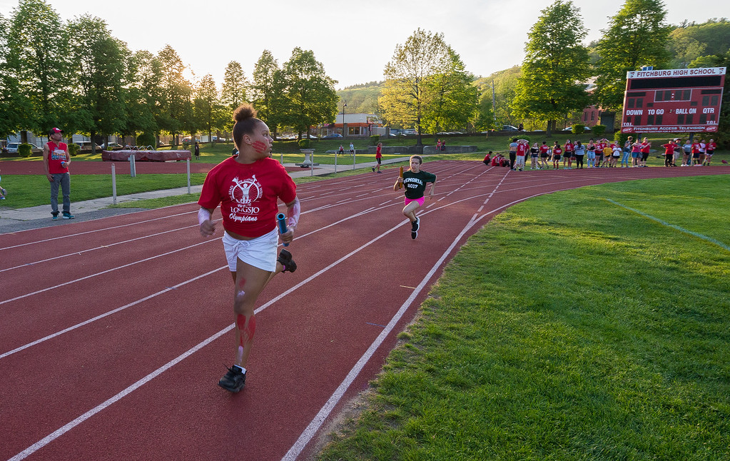 . A Longsjo MIddle School student checks her six as she\'s about to be overtaken by a Memorial Middle School runner at the Junior-Senior Relays at Crocker Field.  SENTINEL&ENTERPRISE/ Jim Marabello