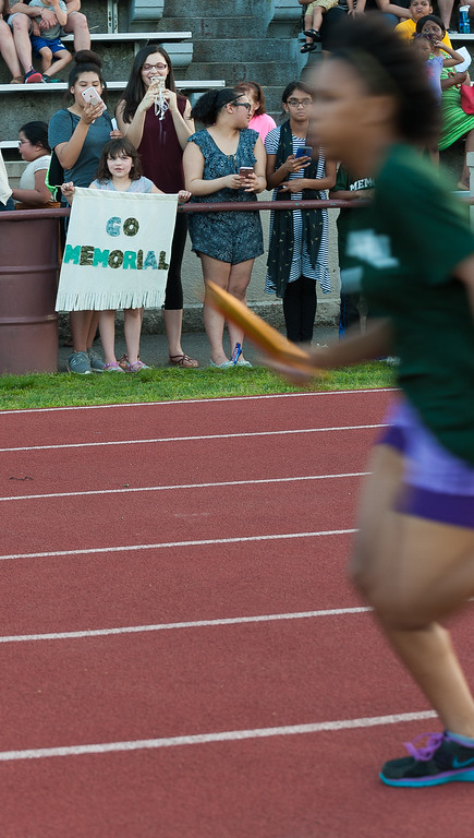. A child holds a banner for a Memorial Middle School runner during the Junior-Senior Relays at Crocker Field.  SENTINEL&ENTERPRISE/ Jim Marabello