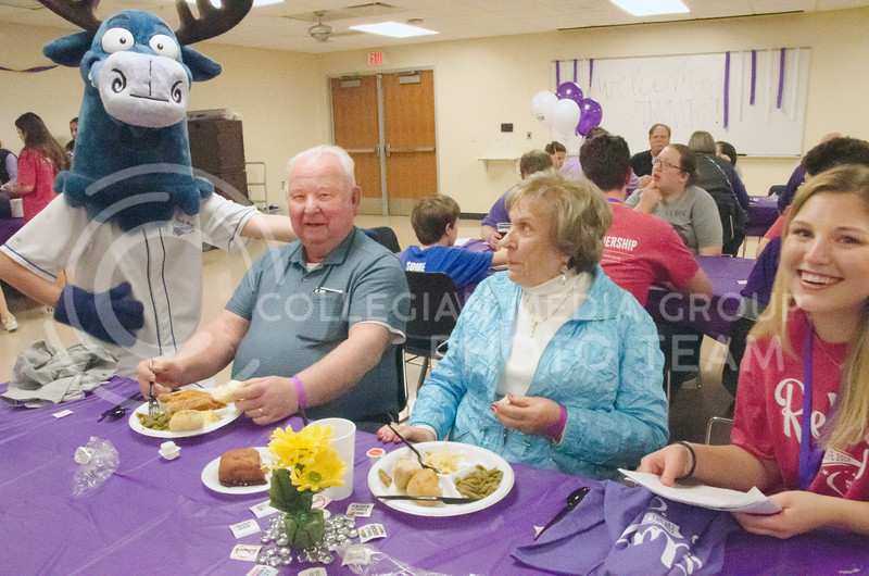 A mascot from The Blue Moose Bar and Grill poses with Ralph and Oma Rogers, from South Dakota, grandparents of Kiersen Graham (right), junior in marketing, at Tori Farwell, senior in biology, at Relay for Life on Saturday, March 2, 2018, at Chester E. Peters Recreation Complex. (Tiffany Roney | Collegian Media Group)