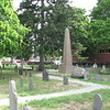 The monument to Brooks is the tall brown obelisk located in the center of the cemetery, along the winding path.