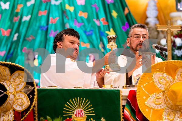 Father Luis Larrea, right, prepares to give communion at Día de la Virgen de Guadalupe feast day and mass, celebrated at St. Peter Claver Parish in Tyler, Texas, on Tuesday, Dec. 12, 2017. Día de la Virgen de Guadalupe honors the belief that Jesus' mother Mary, Mexico's patron saint, appeared to Juan Diego in Mexico City in 1531. (Chelsea Purgahn/Tyler Morning Telegraph)