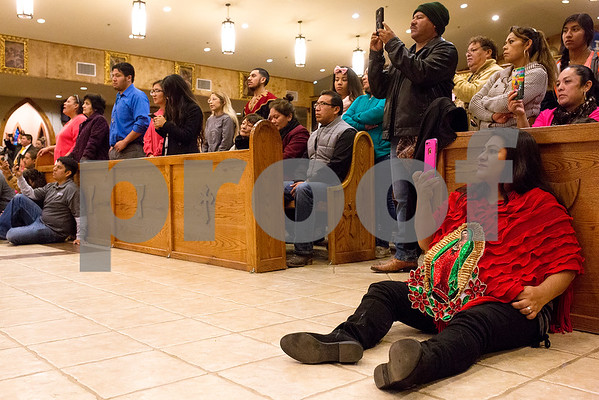 People record Father Luis Luis Larrea, not pictured, speaks at Día de la Virgen de Guadalupe feast day and mass, celebrated at St. Peter Claver Parish in Tyler, Texas, on Tuesday, Dec. 12, 2017. Día de la Virgen de Guadalupe honors the belief that Jesus' mother Mary, Mexico's patron saint, appeared to Juan Diego in Mexico City in 1531.(Chelsea Purgahn/Tyler Morning Telegraph)