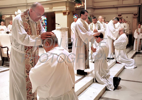Richard Smith is blessed by a fellow priest during the ordination mass at the Cathedral of St. Peter in Wilmington.photo/Don Blake