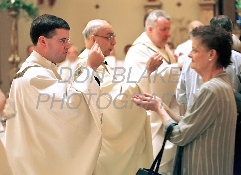 Michael Darcy serves his first communion after being ordained during the mass at the Cathedral of St. Peter in Wilmington.photo/Don Blake