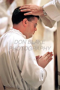 Michael Darcy is blessed by a fellow priest during the ordination mass at the Cathedral of St. Peter in Wilmington.photo/Don Blake