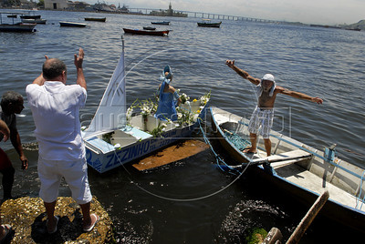 Devotes of Afro-Brazilian religions give offerings into the sea in the Guanabara bay to the African deity of the sea and fertility, Yemanja, Rio de Janeiro, Brazil, February 2, 2012. The festival day corresponds with the Roman Catholic feast of Nuestra Senora de Navegantes, Our Lady of Seafarers, which is also celebrated in Rio de Janeiro. She is also known as the sea-goddess and his devotes give in the sea offerings with flowers, perfumes and wines. Transported by West African slaves to the Americas throughout the hundreds of years of the existence of slavery in the New World. (Austral Foto/Renzo Gostoli)