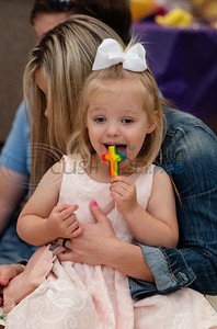 Claire Ducan, 3, sits in her mother Tiffany Ducan's last as she licks a cross shaped sucker during the Family Easter Celebration and Butterfly Release held at Marvin United Methodist Church in downtown Tyler on Sunday April 21, 2019.   (Sarah A. Miller/Tyler Morning Telegraph)
