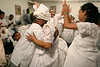 "The mother-of-saint, center, is applauded as she hugs a worshipper during a Candomble ceremony in Rio de Janeiro's working-class district of Bangu, July 24, 2005. Derived from the Yoruba people of West Africa, who were brought to the New World during the African Slave Trade, Candomble seeks harmony with nature. In fact, many Yoruba priests chose to be captured and sold into slavery so that Africans would have spiritual support in the New World. Candomble worships a number of gods or spirits, derived from African deities, known as Orix‡s. An Orixa is a spirit that reflects one of the manifestations of Olodumare (God). Orixas include Shango, Olokun, Elegua, If‡, Osun, Obatala, Ogun, Oko, Soponna, Oya and Esu, among countless others. Over the centuries Candomble has also incorporated many elements from Christianity and African deities were often identified with specific Catholic saints, in part to mask the illegal religion. In the ceremony, led by the mother-of-saint, each child-of-saint (medianic priest) invokes and ""incorporates"" an Orixa, falling into a trance-like state. After recovering from the trance, the priest-spirit performs a dance symbolic of the Orix‡'s attributes, while the father-of-saint (leading male priest) sings about the spirit's deeds.(Australfoto/Douglas Engle)"