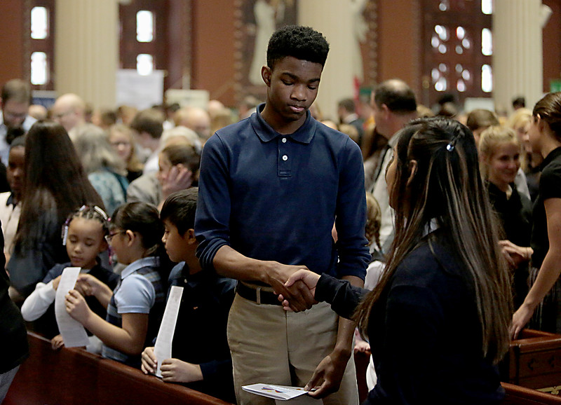 Students greet each other for the Sign of Peace during the Catholic Schools Week Mass at the Cathedral of Saint Peter in Chains in Cincinnati Tuesday, Jan. 29, 2019. (CT Photo/E.L. Hubbard)