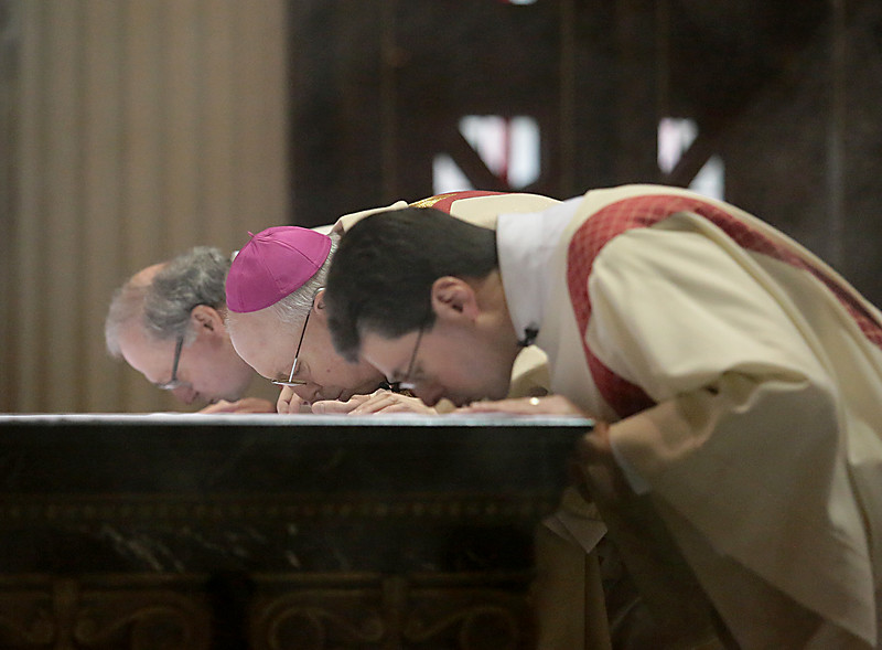 Front to back, Deacon Mark Machuga, Bishop Joseph Binzer, and Deacon Max Schellman kiss the Altar during the Catholic Schools Week Mass at the Cathedral of Saint Peter in Chains in Cincinnati Tuesday, Jan. 29, 2019. (CT Photo/E.L. Hubbard)