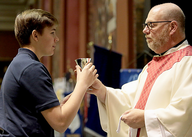 Father Del Staigers, from St. Veronica, offers a student the Blood of Christ during the Catholic Schools Week Mass at the Cathedral of Saint Peter in Chains in Cincinnati Tuesday, Jan. 29, 2019. (CT Photo/E.L. Hubbard)
