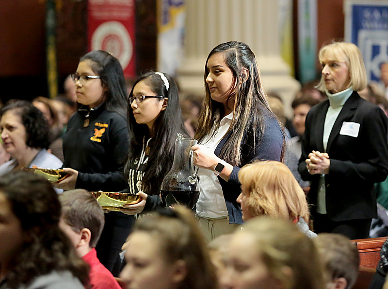 Marlene Gonzalez, Fatima Lowrey, and Milyebi DeLeon Reynoso carry the Gifts during the Catholic Schools Week Mass at the Cathedral of Saint Peter in Chains in Cincinnati Tuesday, Jan. 29, 2019. (CT Photo/E.L. Hubbard)