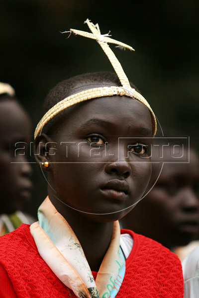 A young girl attends mass in Rumbek in southern Sudan to celebrate the 50th anniversary of the Diocese of Rumbek, Nov. 19, 2005. The mass was to welcome Catholic Archbishop of Khartoum, Cardinal Gabriel Zubeir Wako, the first Sudanese cardinal ever, in a celebration seldom seen before the the Jan. 9, 2005 peace accord was signed. The accord ended a 21-year conflict in the largest nation in Africa, which has only known 11 years of peace since independence from Britain in 1956.  In the accord, the Islamic Arab Sudanese government agreed to give autonomy to the non-Muslim southern Sudan region. After a six year period a referendum will be held to decide on independence or rejoining with the central government. The region has a population of around 9 million and a predominantly rural, subsistence economy. More than 2 million people have died and more than 4 million are internally displaced or have become refugees as a result of the civil war and war-related impacts.(Australfoto/Douglas Engle)