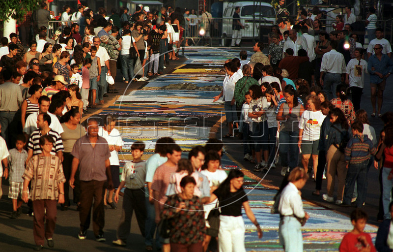 "Church-goers look at one of hundreds of ""carpets"" made of salt, coffee and sawdust on the street in Sao Goncalo, about 15 miles east of Rio de Janeiro, Brazil, Thursday, June 3, 1999. The carpets and a procession are to celebrate Corpus Christi day of the Catholic Church.(Australfoto/Douglas Engle)"