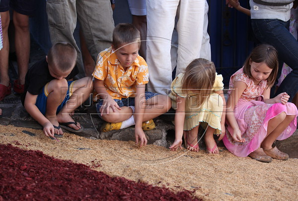 """Waiting for an Easter Sunday procession, children play with the colored sawdust and rice husks, of thematic """"carpets"""" on the streets of the historic city of Ouro Preto in the Brazilian state of Minas Gerais. The """"carpets"""" pave the path were the Easter Sunday procession passes later that day. (Douglas Engle/Australfoto)"""