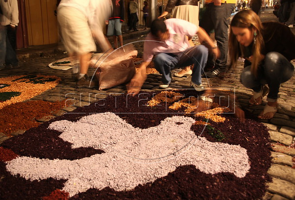 "Worshipers prepare ""carpets"" made of colored sawdust and rice husks on the streets of the historic city of Ouro Preto in the Brazilian state of Minas Gerais. The ""carpets"" pave the path were the Easter Sunday procession passes later that day. (Douglas Engle/Australfoto)"