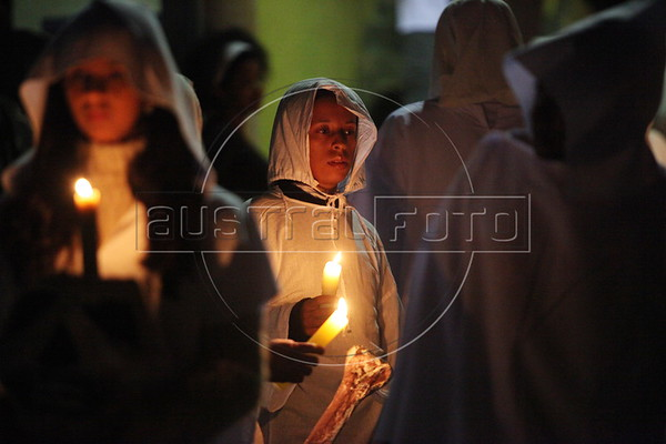 """Dressed in all white and carrying candles and replicas of bones, worshipers participate in the """"Procession of the Souls"""" at 11:55 PM on Good Friday in Mariana in the Brazilian state of Minas Gerais. The procession re-enacts a legend of the city: during holy Week, the dead leave the cemetery in procession to the church. (Douglas Engle/Australfoto)"""
