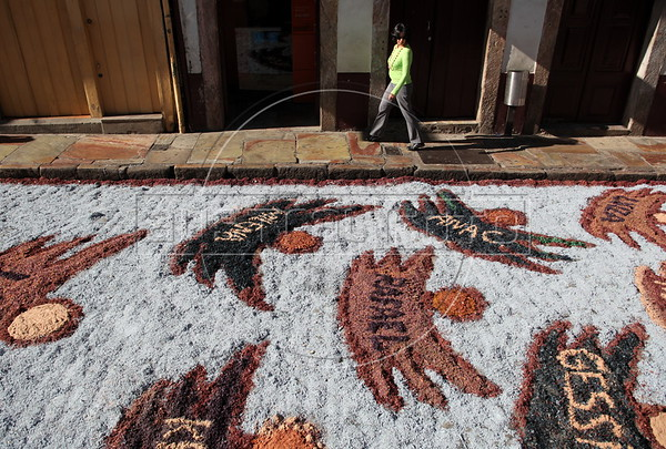 "A woman walks past a  ""carpet"" hororing the victims of the Realengo school shooting, made of colored sawdust and rice husks, on the streets of the historic city of Ouro Preto in the Brazilian state of Minas Gerais. The ""carpets"" pave the path were the Easter Sunday procession passes later that day. (Douglas Engle/Australfoto)"