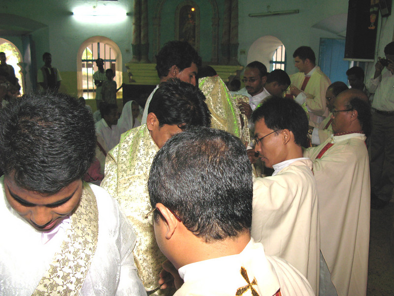 The newly ordained deacons are helped putting on their vestments.