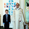 Dusty with Father Bill. The cross behind them is the student's handprints.