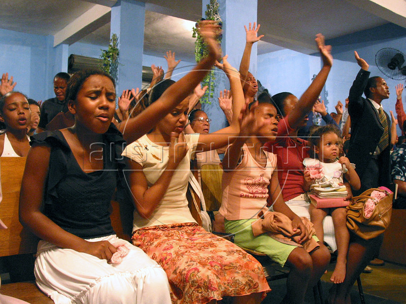 "Church-goers participate in an Assembly of God church service in a slum of Rio de Janeiro.With most state functions absent in Rio's far of neighborhoods, the church pastor and the ""ministers""  find it easy to make converts of drug trafficker and others with their agressive recruitment campaign. (Australfoto/Douglas Engle)"
