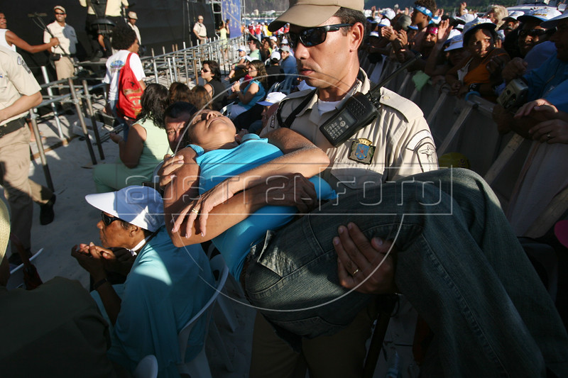"""Police carry off a woman overcome by the heat at an evangelical show on the Botafogo beach in Rio de Janeiro, Brazil, Feb. 4, 2006. Police said 300,000 people attended the service, called """"Show of Faith"""" presented by Evangelical superstar missionary R. R. Soares. While Brazil, with 178 million people, is the world's largest Catholic country, Evangelical Protestants have made significant gains.  According to government figures, the percentage of Catholics fell from 84 percent in 1991 to 74 percent in 2000, while Evangelicals increased from 9 percent to 15 percent during the same period. Some predictions show evangelicals as half the population by 2050. The country's dire poverty explains part of the shift, with Brazil's tens of millions of poor looking for help to ease their misery after 500 years of Roman Catholic domination in the country. Another part of the evangelical appeal is theatrical, which plays well in Brazil.  Soares, who leads International Church of the Grace of God, has become the most the man who appears most on Brazilian television with some 100 hours per week on four free channels. (Australfoto/Douglas Engle)"""