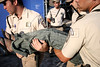 "Police carry off a woman overcome by the heat at an evangelical show on the Botafogo beach in Rio de Janeiro, Brazil, Feb. 4, 2006. Police said 300,000 people attended the service, called ""Show of Faith"" presented by Evangelical superstar missionary R. R. Soares. While Brazil, with 178 million people, is the world's largest Catholic country, Evangelical Protestants have made significant gains.  According to government figures, the percentage of Catholics fell from 84 percent in 1991 to 74 percent in 2000, while Evangelicals increased from 9 percent to 15 percent during the same period. Some predictions show evangelicals as half the population by 2050. The country's dire poverty explains part of the shift, with Brazil's tens of millions of poor looking for help to ease their misery after 500 years of Roman Catholic domination in the country. Another part of the evangelical appeal is theatrical, which plays well in Brazil.  Soares, who leads International Church of the Grace of God, has become the most the man who appears most on Brazilian television with some 100 hours per week on four free channels. (Australfoto/Douglas Engle)"