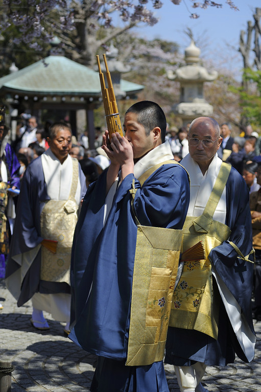 """Another priest plays a """"sho,"""" a kind of mouth organ made from bamboo."""